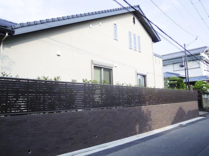 道路面からの プライバシー を守るため、横柄の 木調フェンスに 重厚感あるタイル貼りの塀。