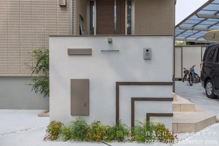 玄関の目隠しを兼ねた大き目の門柱。ポストと宅配ボックス、表札がひと纏まりになっており、足元のミニガーデンも華やかです。