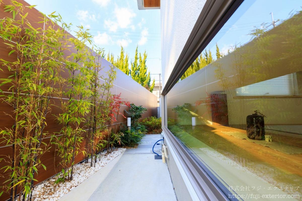 和室の腰窓から見える小庭は、木目調の目隠しがあり、手前にはクロチクを植えました。