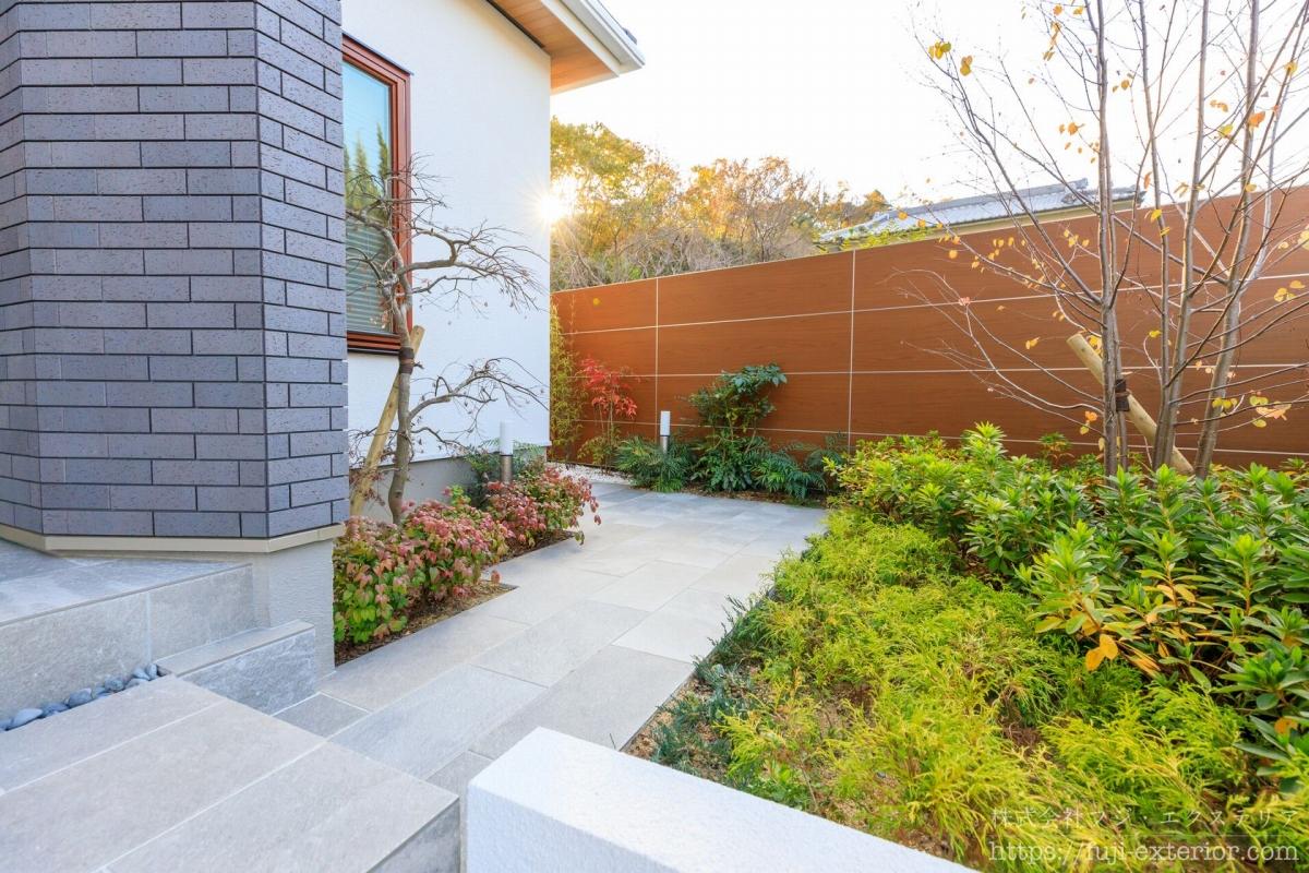 玄関横には、裏に続く小道があり、シダレモミジ 、ヒイラギナンテンなどの様々な植物が植えられています。境界の目隠し塀には、タカショー エバーアートボードを設置し、木調の温かい印象にしました。