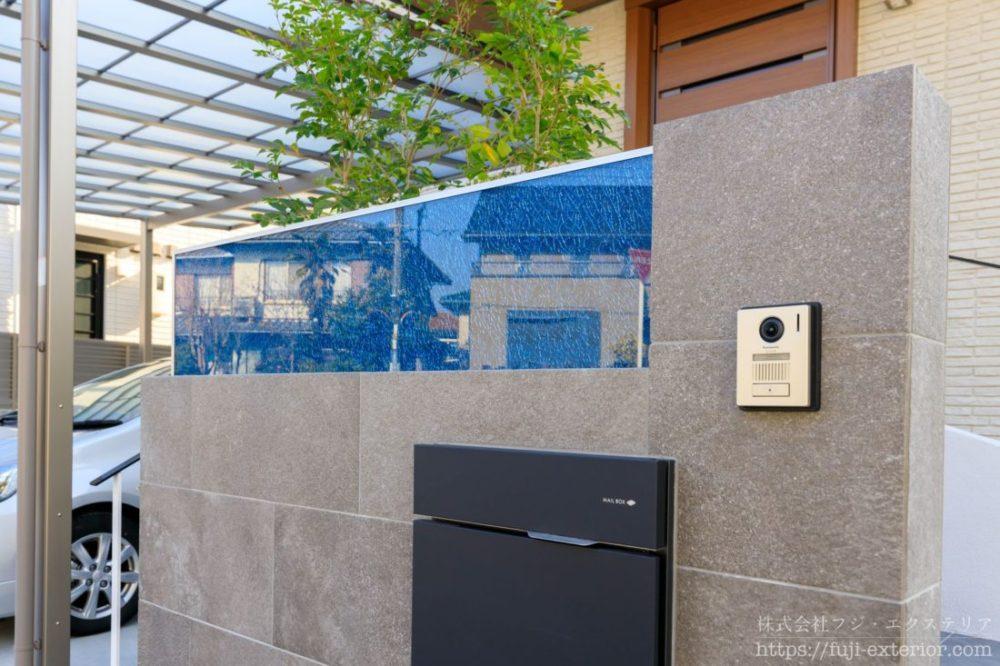 門柱の上部には、ZERO ティンクルⅡというブルーのエクステリアガラスが埋め込まれています。クラッシュ加工したガラスを3層の強化ガラスと2層の飛散防止膜で挟み込んでおり、内部のクラッシュ亀裂に光が乱反射してキラキラと輝き、独特のテクスチャーを作り上げます。そこに文字を彫りこみ、表札にしています。