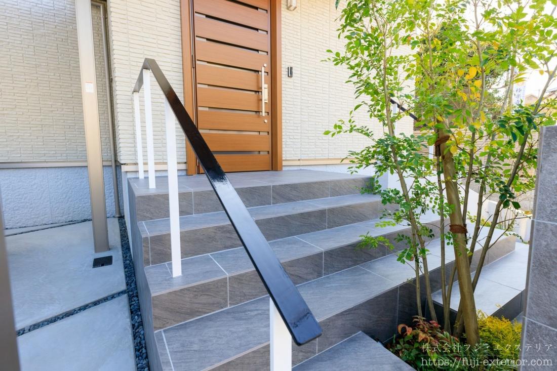 門柱を挟んで左右両方に階段があります。間口が広いので、左右どちらからでも入れるように設計されました。片方の階段には手すりが付いています。小さいお子様が落ちないように、オーダーメイドでアイアンの手すりを作りました。
