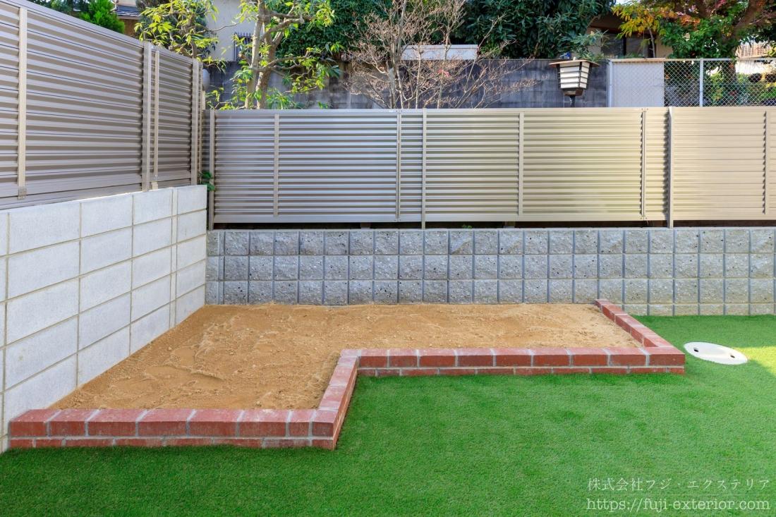 庭の隅には温かみのある赤系レンガで仕切られた家庭菜園スペースとお子様の土の遊び場があります。