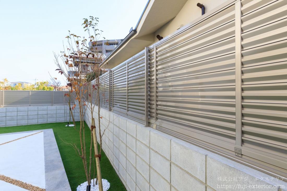 隣地境界には、控壁の不要なブロック6段積みの上にアルミフェンスを全周に設置。フェンスの下の隙間にもアンダーカバーを取り付けて、目隠しとセキュリティは万全です。フェンスは光沢の美しいステンカラーで、シャープな印象です。