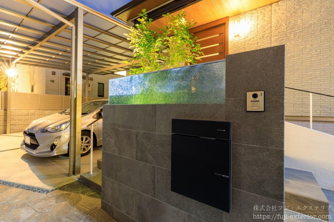 門柱の裏には自動点灯のアッパーライトを付けています。ライトが灯ると、ブルーのガラスと植栽のグリーンが光に透けて重なり合って、絶妙な色合いが生まれます。